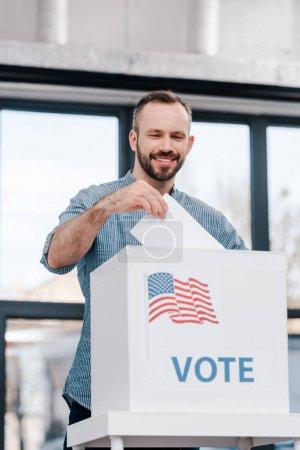 Foto de Feliz hombre que vota y coloca las urnas en las urnas con letras de voto - Imagen libre de derechos