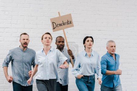 Photo pour Groupe de personnes marchant près de l'homme afro-américain tenant une pancarte avec lettrage demokratie - image libre de droit