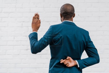 Photo pour Back view of african american diplomat standing with fingers crossed near brick wall - image libre de droit