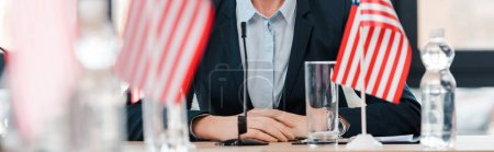 panoramic shot of businesswoman near american flags on table