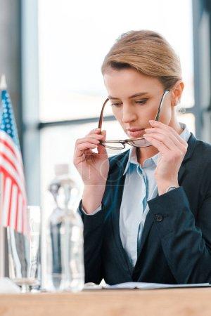 selective focus of attractive diplomat wearing eyeglasses near american flag