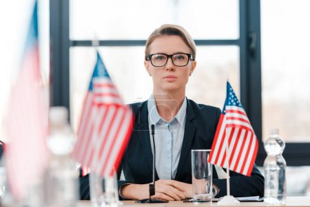 selective focus of attractive diplomat in eyeglasses near american flags on table