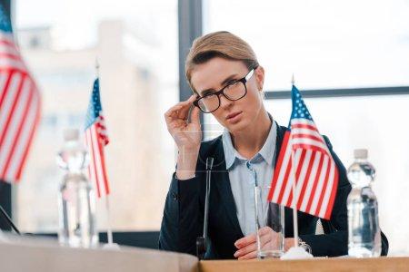 Photo pour Foyer sélectif de beaux diplomates touchant des lunettes près des drapeaux américains - image libre de droit