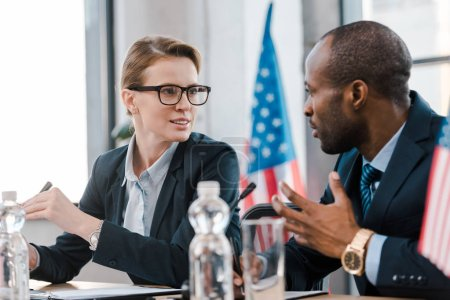 selective focus of attractive diplomat talking with african american representative