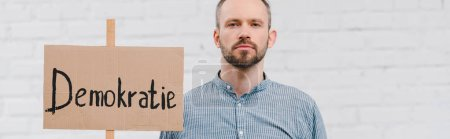Photo for Panoramic shot of bearded citizen holding placard with demokratie lettering near brick wall - Royalty Free Image