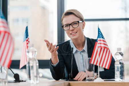 Photo for Smiling diplomat in eyeglasses gesturing while talking near microphone and american flag - Royalty Free Image