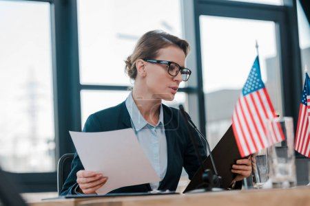 selective focus of attractive diplomat in eyeglasses looking at clipboard near american flags