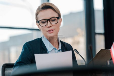 selective focus of attractive diplomat in eyeglasses looking at document