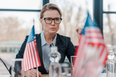 selective focus of patriotic woman in eyeglasses with clenched fist near american flags