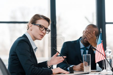 selective focus of woman talking in microphone near african american man covering face