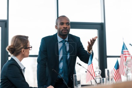 Photo pour L'attention sélective d'un diplomate séduisant regardant un Africain américain en train de gesticuler tout en parlant près de drapeaux d'Amérique - image libre de droit