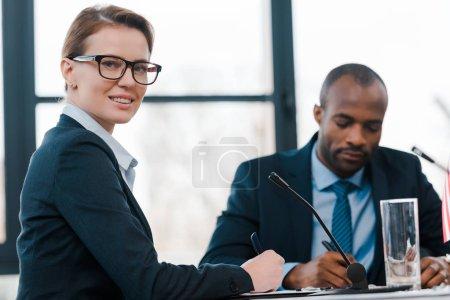 selective focus of happy diplomat looking at camera near african american representative