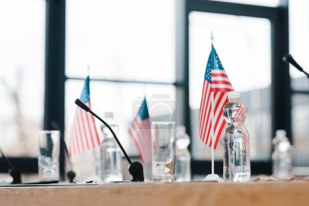 Photo pour Foyer sélectif des drapeaux américains près des verres et des bouteilles avec de l'eau sur la table - image libre de droit