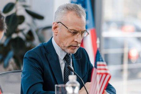 enfoque selectivo de diplomático barbudo en anteojos cerca de banderas americanas
