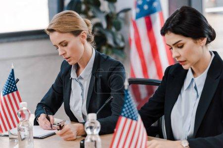 Photo pour Attrayant femme d'affaires écriture près de drapeaux américains - image libre de droit