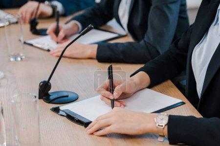 Photo pour Vue recadrée des femmes d'affaires écrivant près des microphones et des lunettes sur la table - image libre de droit