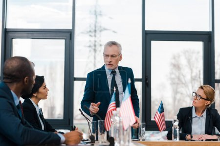Photo pour Focalisation sélective d'un homme d'affaires barbu pointant du doigt un diplomate américain africain à proximité de femmes d'affaires - image libre de droit
