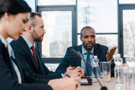 selective focus of handsome african american representative talking near diplomats