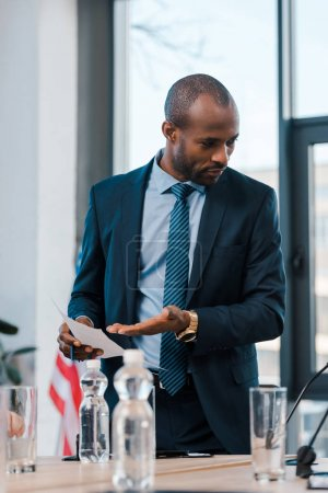 selective focus of african american diplomat gesturing while holding paper