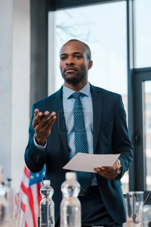 selective focus of handsome african american diplomat gesturing while holding paper