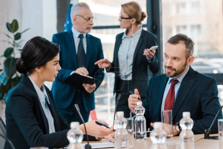 Photo for Selective focus of diplomats talking and gesturing near glasses on table - Royalty Free Image