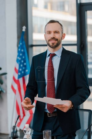 selective focus of happy diplomat in suit holding papers near american flag