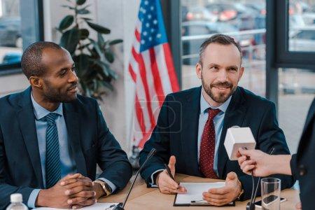 Photo pour Crosse d'un journaliste tenant un microphone près d'heureux diplomates multiculturels - image libre de droit