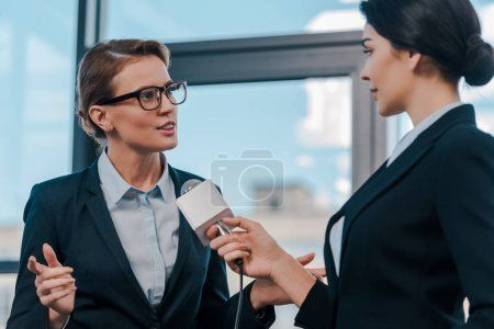 selective focus of journalist holding microphone near attractive diplomat