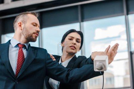 Photo pour Bel homme d'affaires ne montrant aucun geste à journaliste attrayant avec microphone - image libre de droit