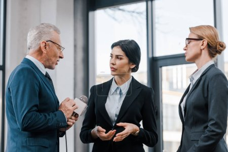 Photo pour Bel homme d'affaires tenant microphone près de belles femmes d'affaires - image libre de droit