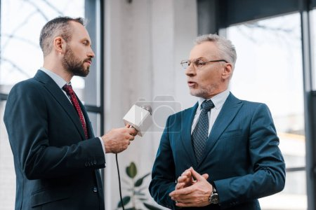 handsome journalist holding microphone near bearded diplomat in glasses