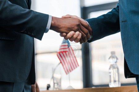 Photo pour Vue recadrée de diplomates multiculturels serrant la main près du drapeau de l'Amérique - image libre de droit
