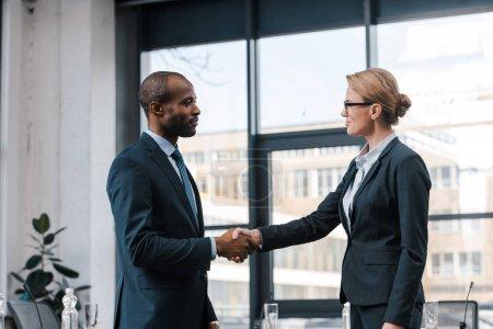 Foto de Vista lateral de la atractiva mujer de negocios estrechando la mano con el hombre de negocios africano-americano. - Imagen libre de derechos