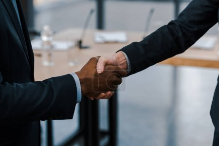 cropped view of businesswoman shaking hands with african american diplomat