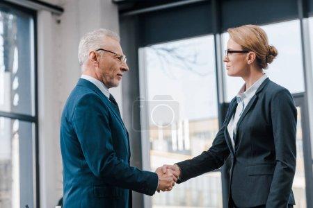 Photo pour Vue de côté d'une femme d'affaires serrant la main avec un homme d'affaires en lunettes - image libre de droit