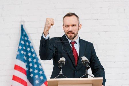 Photo pour Focus sélectif de haut-parleur émotionnel à poing serré parlant près des micros et du drapeau américain - image libre de droit