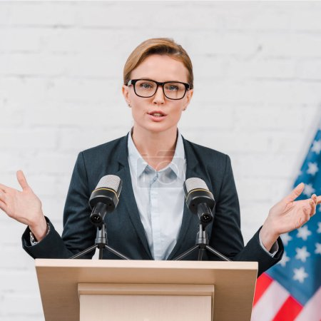 attractive speaker in glasses gesturing while talking near microphones