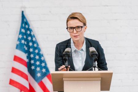 Photo pour Haut-parleur attrayant dans des lunettes parlant près des microphones et drapeau américain - image libre de droit