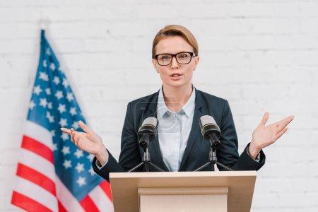 Photo pour Beau haut-parleur dans des lunettes gestuelle tout en parlant près des microphones - image libre de droit