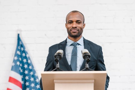 Photo for Happy african american speaker standing near microphones and american flag - Royalty Free Image