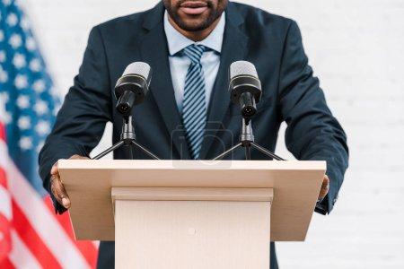 Photo pour Vue recadrée de haut-parleur afro-américain parlant près des microphones et drapeau américain - image libre de droit