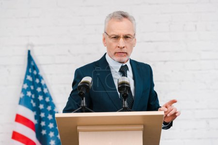 Photo for Bearded speaker in glasses pointing with finger near microphones and american flag - Royalty Free Image