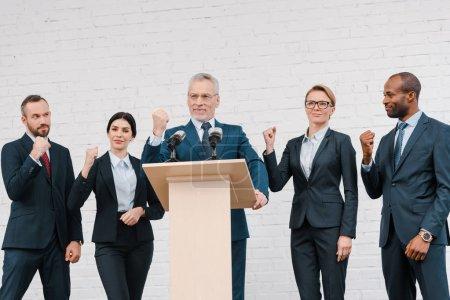 Photo pour Heureux orateur dans les lunettes et les hommes d'affaires multiculturels et les femmes d'affaires montrant les poings serrés - image libre de droit