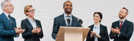 Photo pour Plan panoramique d'hommes d'affaires et de femmes d'affaires applaudissant au conférencier afro-américain - image libre de droit
