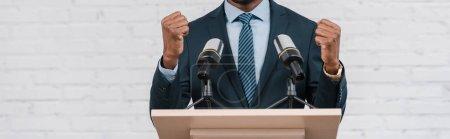 Photo pour Prise de vue panoramique de haut-parleur afro-américain debout avec des poings serrés près des microphones - image libre de droit