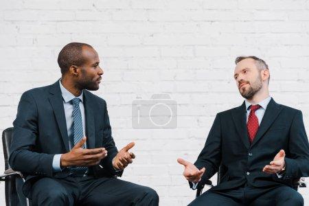 Photo pour Beau homme d'affaires afro-américain gesticulant tout en regardant diplomate - image libre de droit