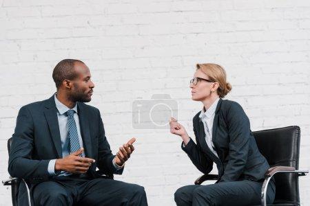 Photo pour Vue latérale d'un homme d'affaires afro-américain gesticulant près d'une femme d'affaires dans des lunettes assises sur une chaise - image libre de droit