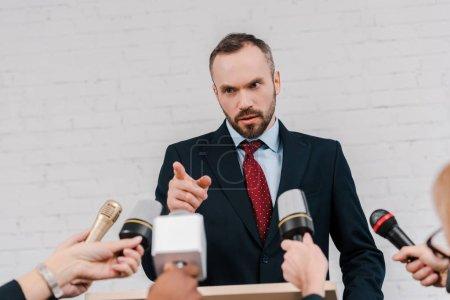 Photo pour Photo prise d'un journaliste tenant un microphone près d'un diplomate barbu pointant du doigt - image libre de droit