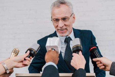 Foto de La visión descabellada de los periodistas que tienen micrófonos cerca de un diplomático feliz en gafas - Imagen libre de derechos