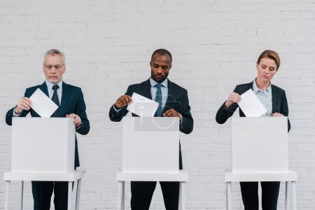 multicultural voters putting ballots in voting boxes